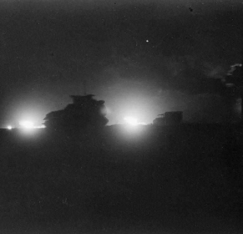 Vehicles silhouetted against the flash of artillery